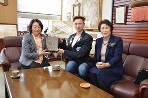川俣市長(左)からプレゼントを受け取るケイルブさん(中央)