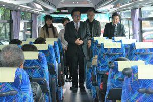 バスで都内の自動車関連企業の見学ツアーに出発する子どもたちにあいさつする中尾さん(中央)