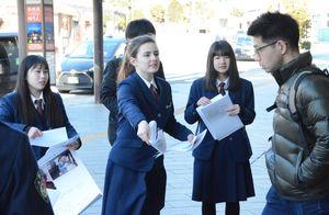 チラシを配布して情報提供を呼び掛ける鹿沼東高の生徒ら=9日午前、東武日光駅