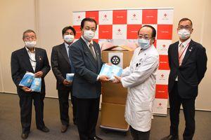 本多院長にサージカルマスクを手渡す野澤会長(左から3人目)
